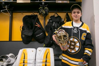 """Make-A-Wish recipient Jimmy Bjorkman of West Salem, Wisconsin picks up Boston Bruins goaltender Tuuka Rask's mask in the Boston Bruins locker room after a hockey game between the Boston Bruins and the Montreal Canadiens at TD Garden in Boston, Massachusetts Sunday, February 8, 2015."""