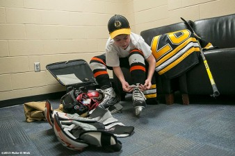 """Make-A-Wish recipient Jimmy Bjorkman of West Salem, Wisconsin suits up before a hockey game between the Boston Bruins and the Montreal Canadiens at TD Garden in Boston, Massachusetts Sunday, February 8, 2015."""