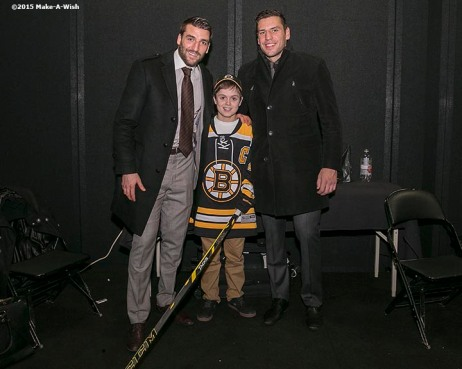 """Make-A-Wish recipient Jimmy Bjorkman of West Salem, Wisconsin meets Boston Bruins players Patrice Bergeron and Milan Lucic after a hockey game between the Boston Bruins and the Montreal Canadiens at TD Garden in Boston, Massachusetts Sunday, February 8, 2015."""