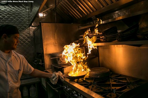 """A chef cooks as flames rise into a newly installed Eco Thermal Filter System in the kitchen of The Stockyard Steakhouse restaurant in Brighton, Massachusetts Tuesday, February 10, 2015."""