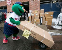 """Mascot Wally the Green Monster loads boxes into the truck during Boston Red Sox truck day Thursday, February 12, 2015 at Fenway Park in Boston, Massachusetts."""