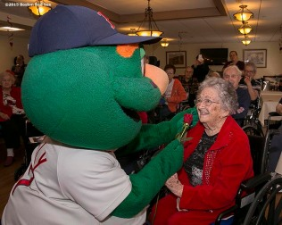 """Mascot Wally the Green Monster greets a resident during a Boston Red Sox Valentine's Day caravan to retirement and assisted living communities throughout greater Boston Friday, February 13, 2015."""