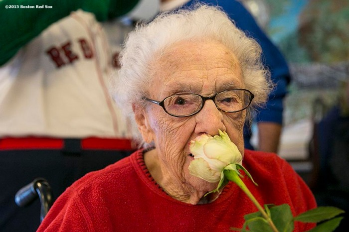 """""""A resident poses for a photograph with a rose during a Boston Red Sox Valentine's Day caravan to retirement and assisted living communities throughout greater Boston Friday, February 13, 2015."""""""