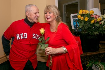 """Former Boston Red Sox player Ted Lepcio gives a resident a rose during a Boston Red Sox Valentine's Day caravan to retirement and assisted living communities throughout greater Boston Friday, February 13, 2015."""