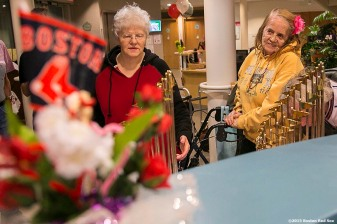 """Residents observe the World Series trophies during a Boston Red Sox Valentine's Day caravan to retirement and assisted living communities throughout greater Boston Friday, February 13, 2015."""