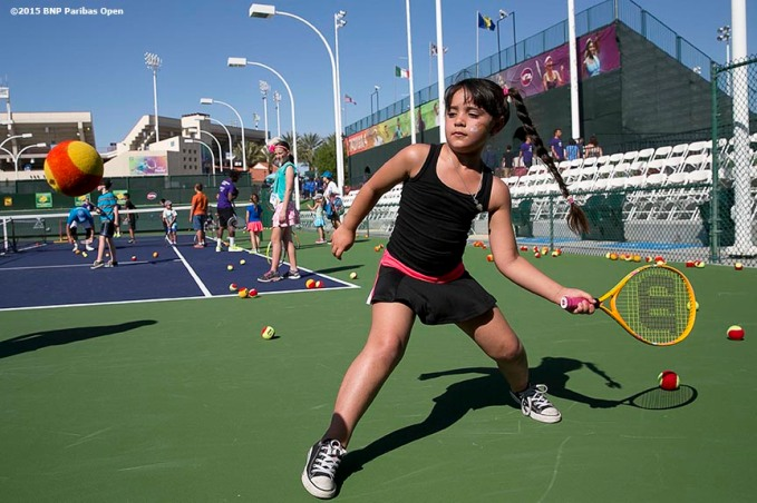 """A girl hits a forehand during Kids Day at the Indian Wells Tennis Garden in Indian Wells, California Saturday, March 7, 2015."""