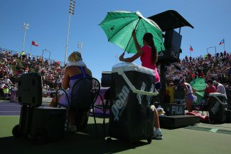 """Ball kids hold umbrellas over Simona Halep and Daria Gavrilova during their match at Stadium 3 at the Indian Wells Tennis Garden in Indian Wells, California on Friday, March 13, 2015."""