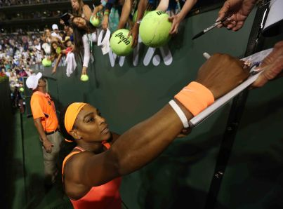 """Serena Williams signs autographs for fans following her win against Monica Niculescu during their match at Stadium 1 at the Indian Wells Tennis Garden in Indian Wells, California on Friday, March 13, 2015."""