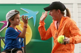 """Lisa Raymond high fives a young fan during a Tennis Talk at the Indian Wells Tennis Garden in Indian Wells, California Wednesday, March 18, 2015."""