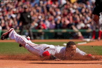 """""""Boston Red Sox center fielder Mookie Betts dives into third base during the first inning of a home opening game against the Washington Nationals Monday, April 13, 2015 at Fenway Park in Boston, Massachusetts."""""""