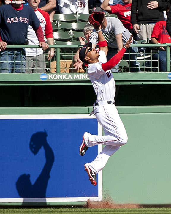 """Boston Red Sox center fielder Mookie Betts leaps as catches a home run ball over the outfield wall during the first inning of a home opening game against the Washington Nationals Monday, April 13, 2015 at Fenway Park in Boston, Massachusetts."""