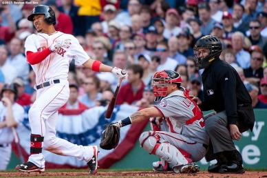 """""""Boston Red Sox center fielder Mookie Betts hits a three run home run during the second inning of a home opening game against the Washington Nationals Monday, April 13, 2015 at Fenway Park in Boston, Massachusetts."""""""