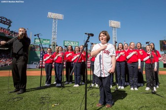 """Jane Richard, sister of Boston Marathon bombing victim Martin Richard, leans the St. Ann's Children's Choir in singing the National Anthem during a pre-game ceremony before the Boston Red Sox 2015 home opener against the Washington Nationals Monday, April 13, 2015 at Fenway Park in Boston, Massachusetts."""