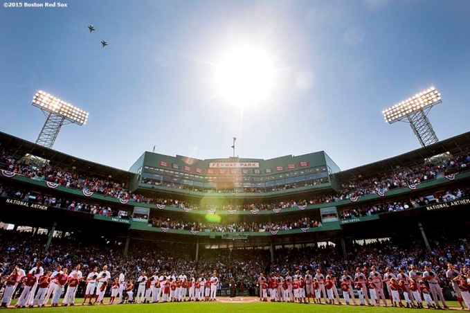 """A flyover is held as members of the Boston Red Sox and Washington Nationals line up alongside kids during a pre-game ceremony before the Boston Red Sox 2015 home opener against the Washington Nationals Monday, April 13, 2015 at Fenway Park in Boston, Massachusetts."""