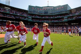 """""""Kids run onto the field during a pre-game ceremony before the Boston Red Sox 2015 home opener against the Washington Nationals Monday, April 13, 2015 at Fenway Park in Boston, Massachusetts."""""""