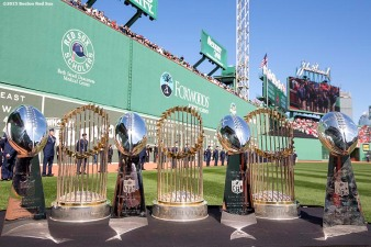 """The Boston Red Sox World Series trophies and the New England Patriots Super Bowl trophies are displayed during a pre-game ceremony before the Boston Red Sox 2015 home opener against the Washington Nationals Monday, April 13, 2015 at Fenway Park in Boston, Massachusetts."""