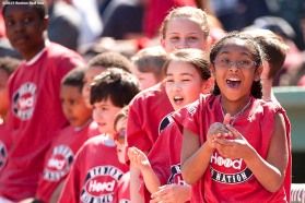 """Kids react as they take the field with players during a pre-game ceremony before the Boston Red Sox 2015 home opener against the Washington Nationals Monday, April 13, 2015 at Fenway Park in Boston, Massachusetts."""