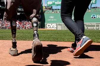 """Boston Marathon bombing survivor Jeff Bauman walks toward the pitchers mound before throwing out the ceremonial first pitch before a game against the Washington Nationals at Fenway Park in Boston, Massachusetts Wednesday, April 15, 2015."""