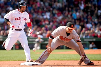 """Boston Red Sox right fielder Shane Victorino beats out an infield single as first baseman Chris Davis makes an error during the fourth inning of a game against the Baltimore Orioles at Fenway Park in Boston, Massachusetts Sunday, April 19, 2015."""