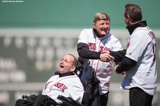 """Marathon runners Dick and Rick Hoyt and Bryan Lyons greet each other before throwing out the cermonial first pitch before a game between the Boston Red Sox and the Baltimore Orioles at Fenway Park in Boston, Massachusetts Sunday, April 19, 2015."""