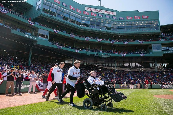"""Marathon runners Dick and Rick Hoyt and Bryan Lyons walk toward the mound before throwing out the cermonial first pitch before a game between the Boston Red Sox and the Baltimore Orioles at Fenway Park in Boston, Massachusetts Sunday, April 19, 2015."""