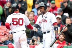 """Boston Red Sox center fielder Mookie Betts high fives left fielder Hanley Ramirez as he scores during the first inning of a game against the Baltimore Orioles at Fenway Park in Boston, Massachusetts Monday, April 20, 2015."""