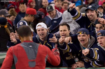 """Members of the Trinity University hockey team cheer as Boston Red Sox center fielder Mookie Betts walks off the field after hitting a game winning walk-off single against the Toronto Blue Jays at Fenway Park in Massachusetts Monday, April 27, 2015."""