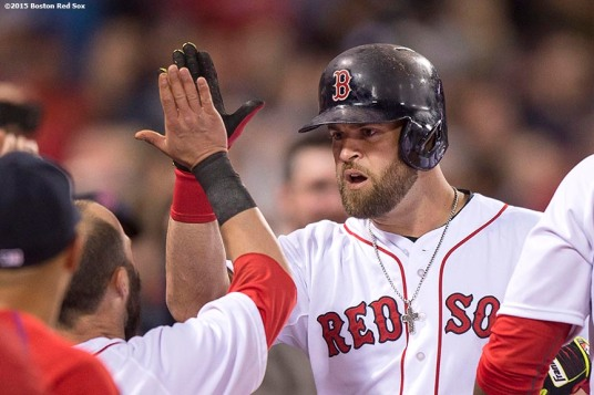 """Boston Red Sox first baseman Mike Napoli high fives teammates after hitting a three run home run during the sixth inning of a game against the New York Yankees at Fenway Park in Boston, Massachusetts Sunday, May 3, 2015."""