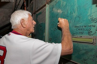 """Former Boston Red Sox left fielder Carl Yastrzemski signs inside the Green Monster scoreboard during a 1975 40 year reunion pre-game ceremony before a game between the Boston Red Sox and the Tampa Bay Rays at Fenway Park in Boston, Massachusetts Tuesday, May 5, 2015."""