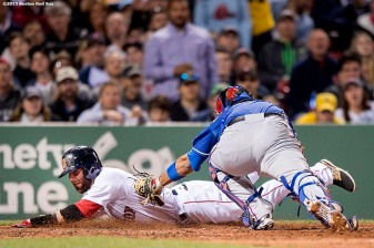 """Boston Red Sox second baseman Dustin Pedroia is tagged out by catcher Carlos Corporan as he slides into home plate during the fourth inning of a game against the Texas Rangers at Fenway Park in Boston, Massachusetts Thursday, May 21, 2015."""