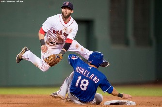 """Boston Red Sox second baseman Dustin Pedroia turns a double play during the seventh inning of a game against the Texas Rangers at Fenway Park in Boston, Massachusetts Thursday, May 21, 2015."""