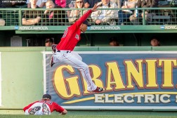 """Boston Red Sox center fielder Mookie Betts jumps over right fielder Brock Holt during the first inning of the second game of a day-night double header against the Minnesota Twins at Fenway Park in Boston, Massachusetts Wednesday, June 3, 2015."""