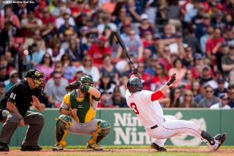 """Boston Red Sox catcher Sandy Leon ducks out of the way of a pitch during the eighth inning of a game against the Oakland Athletics at Fenway Park in Boston, Massachusetts Sunday, June 7, 2015."""