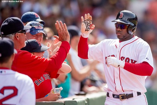 """Boston Red Sox center fielder Rusney Castillo high fives teammats after hitting a solo home run during the eighth inning of a game against the Oakland Athletics at Fenway Park in Boston, Massachusetts Sunday, June 7, 2015."""