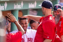 """Boston Red Sox shortstop Xander Bogaerts high fives teammates after scoring during the inning of a game against the Oakland Athletics at Fenway Park in Boston, Massachusetts Sunday, June 7, 2015."""