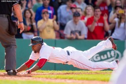 """""""Boston Red Sox outfielder Alejandro De Aza dives into home plate as he scores during the eighth inning of a game against the Oakland Athletics at Fenway Park in Boston, Massachusetts Sunday, June 7, 2015. It was his first at bat as a member of the Boston Red Sox."""""""