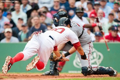 """Boston Red Sox center fielder Mookie Betts dives into home plate as he scores during the sixth inning of a game against the Atlanta Braves at Fenway Park in Boston, Massachusetts Tuesday, June 16, 2015."""