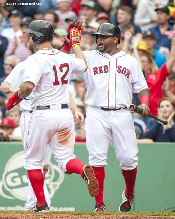 """Boston Red Sox third baseman Pablo Sandoval and first baseman Mike Napoli high five after scoring during the sixth inning of a game against the Atlanta Braves at Fenway Park in Boston, Massachusetts Tuesday, June 16, 2015."""