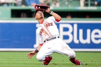 """Boston Red Sox center fielder Mookie Betts slips as he catches a fly ball during the seventh inning of a game against the Atlanta Braves at Fenway Park in Boston, Massachusetts Tuesday, June 16, 2015."""