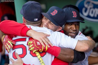 """""""Boston Red Sox first base coach Brian Butterfield, pitcher Justin Masterson, and designated hitter David Ortiz hug each other before a game against the Baltimore Orioles at Fenway Park in Boston, Massachusetts Wednesday, June 24, 2015."""""""