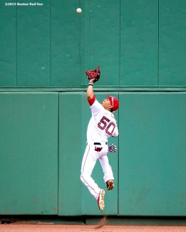 """Boston Red Sox center fielder Mookie Betts jumps as he catches a fly ball during the first inning of a game against the Houston Astros at Fenway Park in Boston, Massachusetts Saturday, July 4, 2015."""