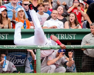"""Boston Red Sox third baseman Pablo Sandoval flips over the visitor's dugout as he catches a fly ball during the fourth inning of a game against the Houston Astros at Fenway Park in Boston, Massachusetts Saturday, July 4, 2015."""