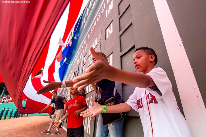 """""""A boy reaches out to catch the American flag as it is dropped over the Green Monster before a game between the Boston Red Sox and the Houston Astros at Fenway Park in Boston, Massachusetts Saturday, July 4, 2015."""""""