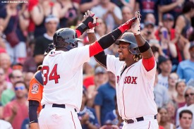 """Boston Red Sox left fielder Hanley Ramirez high fives designated hitter David Ortiz after hitting a go ahead two run home run during the seventh inning of a game against the Houston Astros at Fenway Park in Boston, Massachusetts Sunday, July 5, 2015."""
