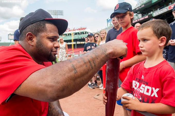 """Boston Red Sox third baseman Pablo Sandoval signs a bat for a young fan before a game against the Miami Marlins at Fenway Park in Boston, Massachusetts Wednesday, July 8, 2015."""