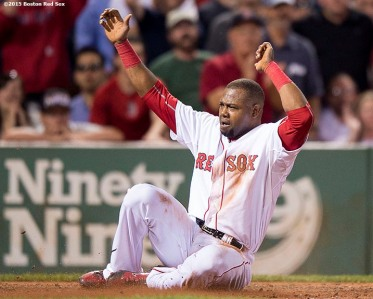 """""""Boston Red Sox left fielder Alejandro De Aza slides as he scores on an overthrown ball during the seventh inning of a game against the Miami Marlins at Fenway Park in Boston, Massachusetts Wednesday, July 8, 2015."""""""