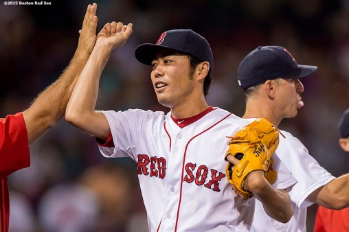 """Boston Red Sox pitcher Koji Uehara high fives teammates after a game against the Miami Marlins at Fenway Park in Boston, Massachusetts Wednesday, July 8, 2015."""