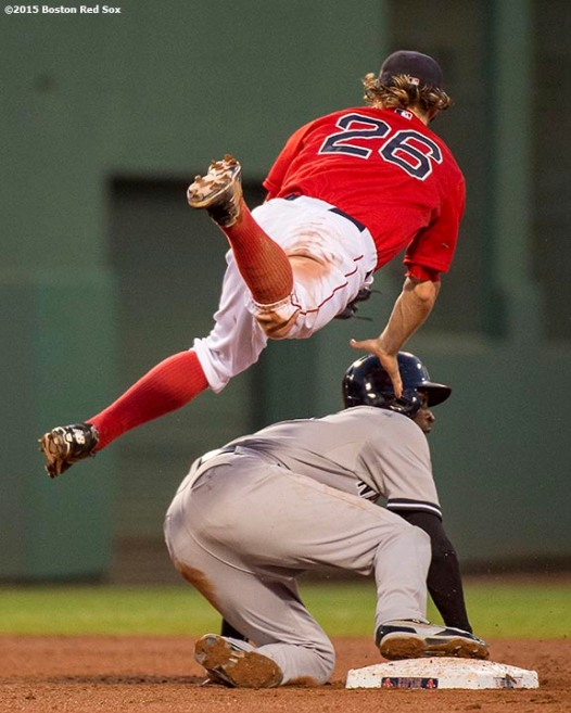"""""""Boston Red Sox second baseman Brock Holt jumps as he catches a ball during the fourth inning of a game against the New York Yankees at Fenway Park in Boston, Massachusetts Friday, July 10, 2015."""""""