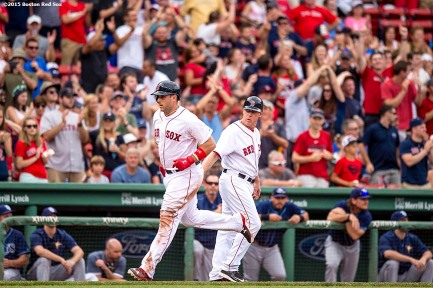 """Boston Red Sox third baseman Travis Shaw high fives third base coach Brian Butterfield after hitting a home run during the eighth inning of a game against the Tampa Bay Rays at Fenway Park in Boston, Massachusetts Saturday, August 1, 2015."""
