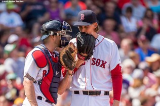 """Boston Red Sox pitcher Henry Owens and catcher Blake Swihart meet during a mound visit during fourth the inning of a game against the Seattle Mariners at Fenway Park in Boston, Massachusetts Sunday, August 16, 2015."""